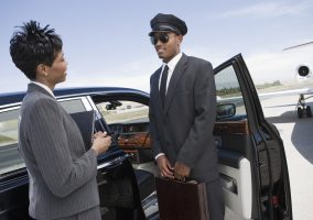 Mid-adult businesswoman and mid-adult chauffeur standing  in front of limousine and talking.