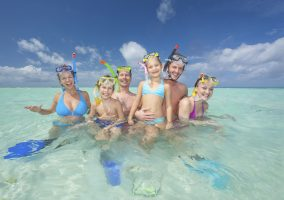happy families with snorkeling gear in turquoise lagoon